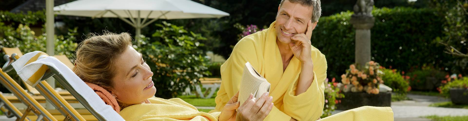 Paar in gelben Bademäntel auf einer Liege im Detail