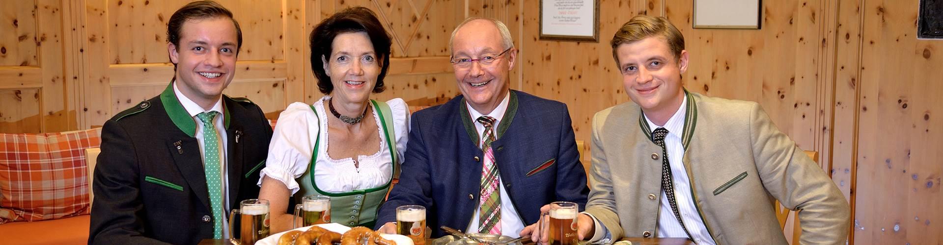 Gastgeber-Familie mit Brettljause und Bier im Portrait