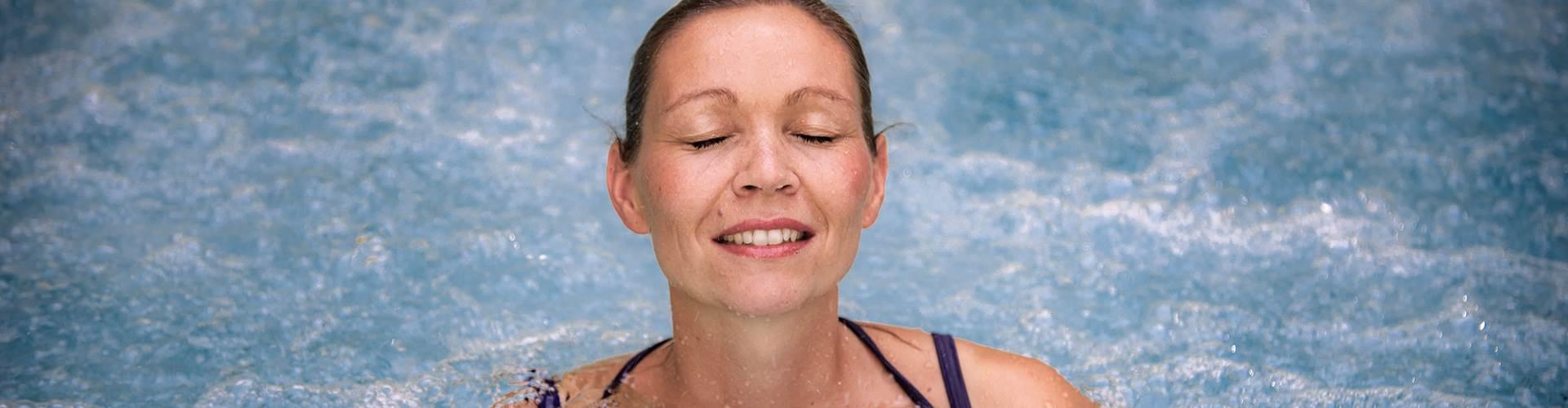 Frau in Thermalbad mit geschlossenen Augen im Portrait