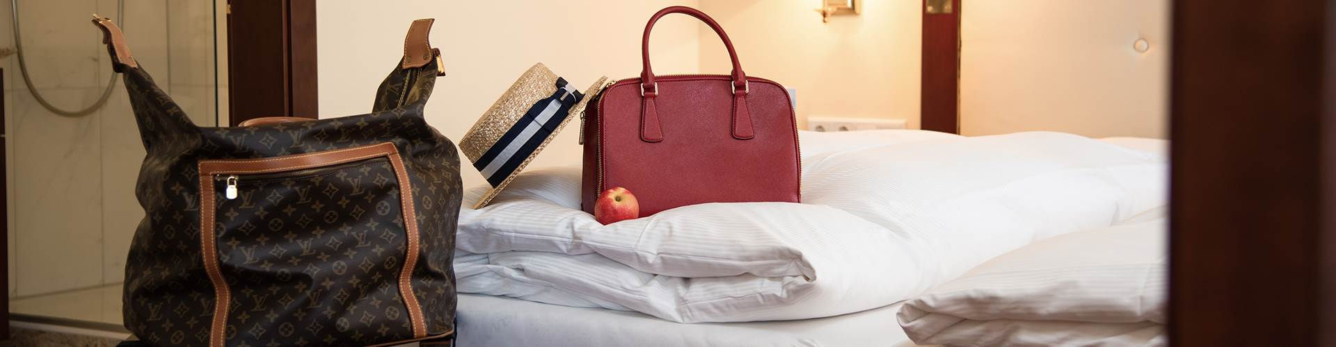 Handtaschen im Detail auf einem Hotelbett