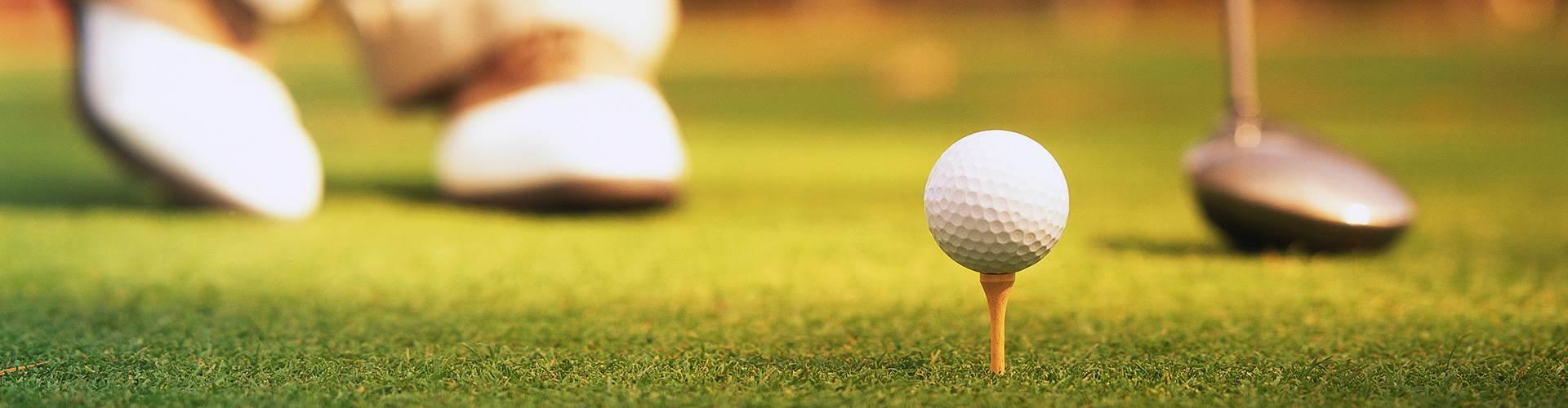 Golfball auf Tee, Golfschläger und Golfschuhe im Detail