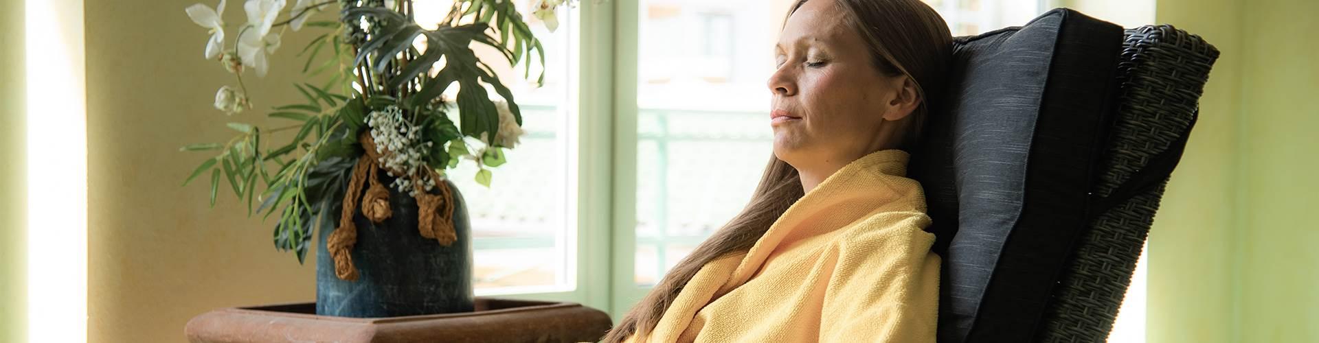 Frau in gelbem Bademantel entspannt auf einem Stuhl