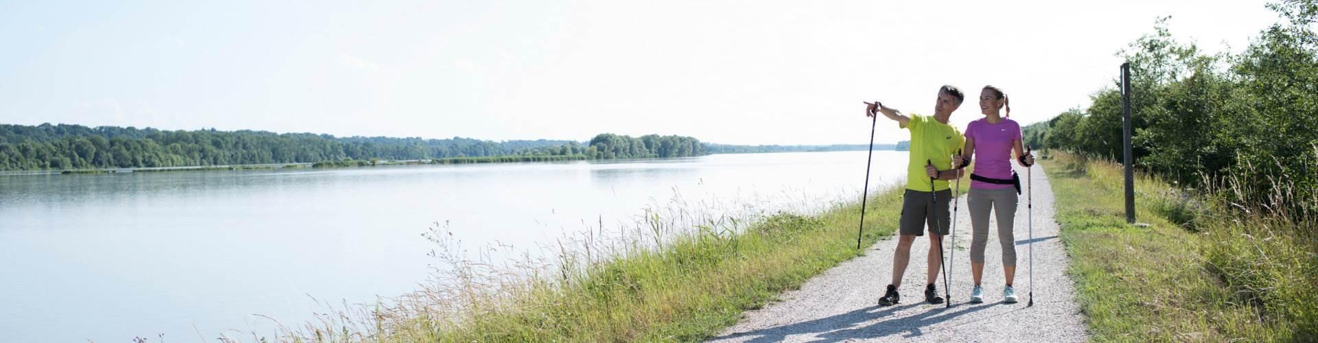 Paar beim Nordic Walking an einem Fluss